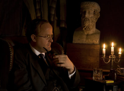 Photograph of Robert Lloyd Parry with pipe and candles illustrating performance