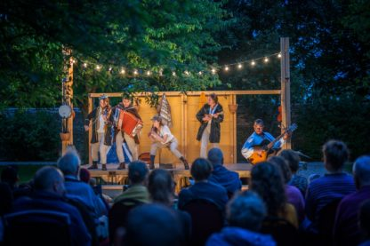 Image of stage and performers outdoors in evening